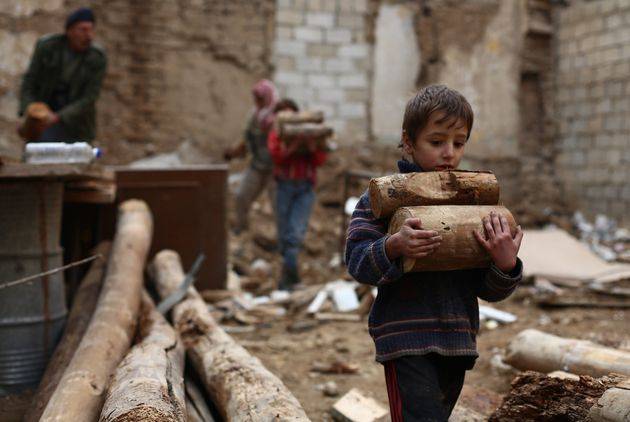 A Syrian boy carries firewood for cooking and heating in the besieged city of Douma, Syria, on November...