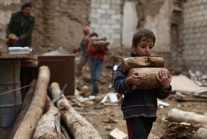 A Syrian boy carries firewood for cooking and heating in the besieged cityof Douma, Syria, on November 29, 2014. Douma,
