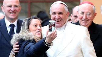 ROME, ITALY - FEBRUARY 08:  Pope Francis poses for a selfie with a the faithful as he pays a visit to the Roman parish of St. Michael the Archangel in Pietralata on February 8, 2015 in Rome, Italy. Following the Angleus prayer on Sunday, Pope Francis spoke about first International Day of Prayer and Awareness against Human Trafficking. The Day of Prayer occurs on 8 February, the liturgical memorial of St. Josephine Bakhita, a Sudanese sister who, as a child, was herself a victim of slavery and human trafficking.  (Photo by Franco Origlia/Getty Images)