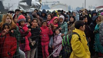 Migrants queue for food at a makeshift camp at the Greek-Macedonian border, near the Greek village of Idomeni on March 15, 2016, where thousands of refugees and migrants are stranded by the Balkan border blockade. Some 1,500 migrants who managed to cross into Macedonia, despite the border being closed to them for a week, have been sent back to Greece by Macedonian troops, officials said. The German and Greek leaders blasted Balkan countries for shutting their borders to migrants ahead of an EU ministers meeting on March 10. Greek authorities said there were 41,973 asylum seekers in the country, including some 12,000 stuck at Idomeni on the closed Macedonian border.  / AFP / DANIEL MIHAILESCU        (Photo credit should read DANIEL MIHAILESCU/AFP/Getty Images)
