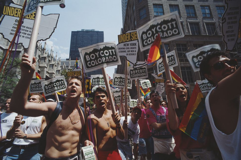 "Men and women carry placards that read ""Boycott Colorado"" at the Gay Pride parade in New York City in June of 1994."