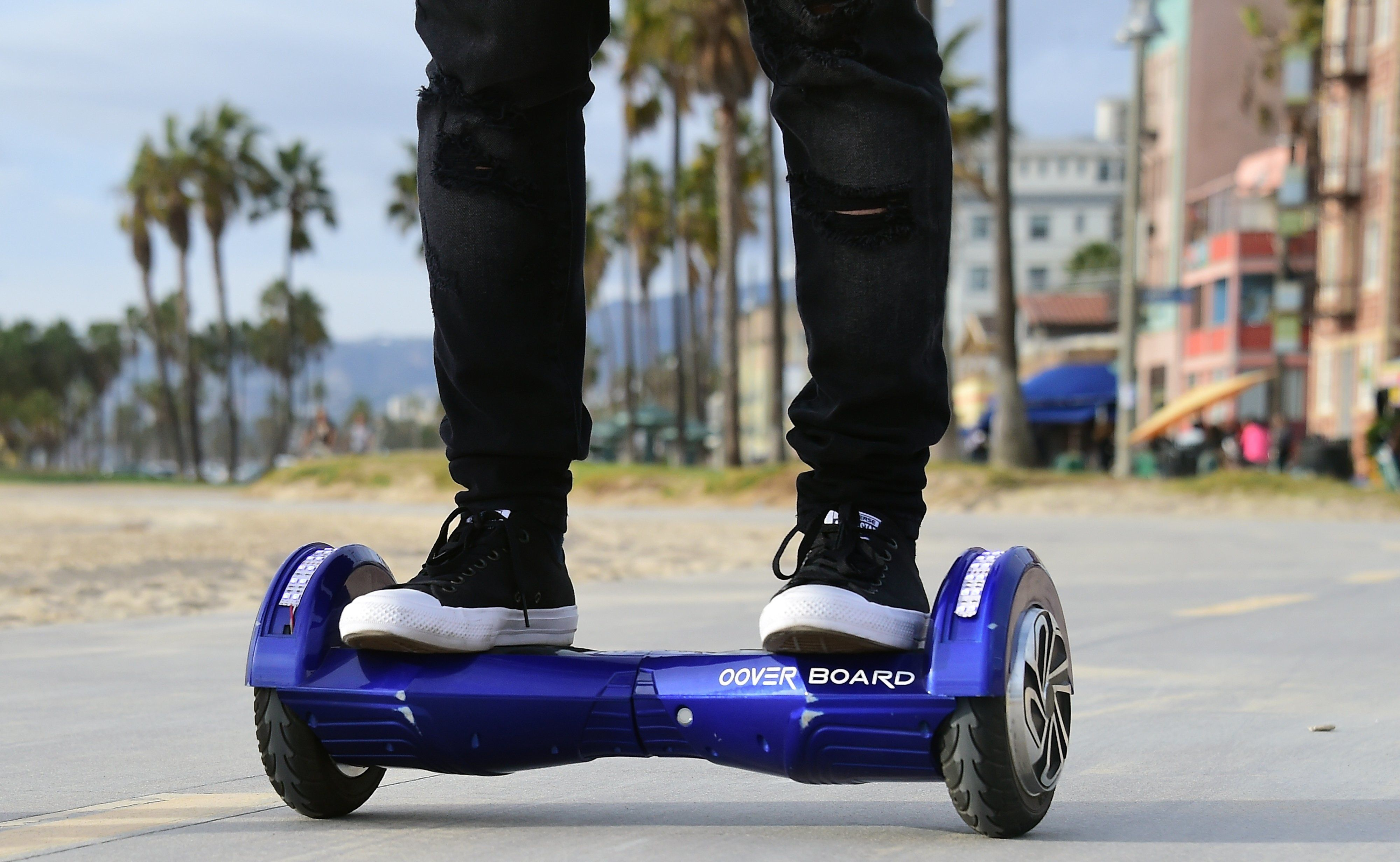 Michael Tran uses his hoverboard on the Venice Beach Boardwalk on December 10, 2015. The hot item on many holiday lists will help you zip around town, the shopping mall and from one end of the workplace to another.These so-called 'hoverboards' or self-balancing electric scooters, are surging in popularity in the first season where they have been available at relatively affordable prices -- as low as $300 for some models. AFP PHOTO/ FREDERIC J. BROWN / AFP / FREDERIC J. BROWN        (Photo credit should read FREDERIC J. BROWN/AFP/Getty Images)
