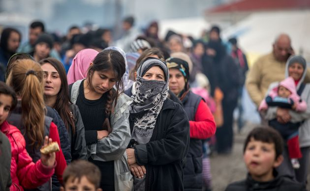 People wait for food aid at the Idomeni refugee camp on the Greek Macedonia border on March 16, 2016...