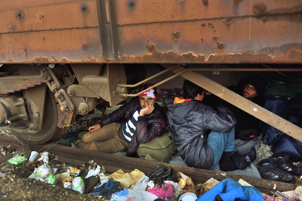 Newly arrived refugees and migrants take shelter under a train carriage in the camp.
