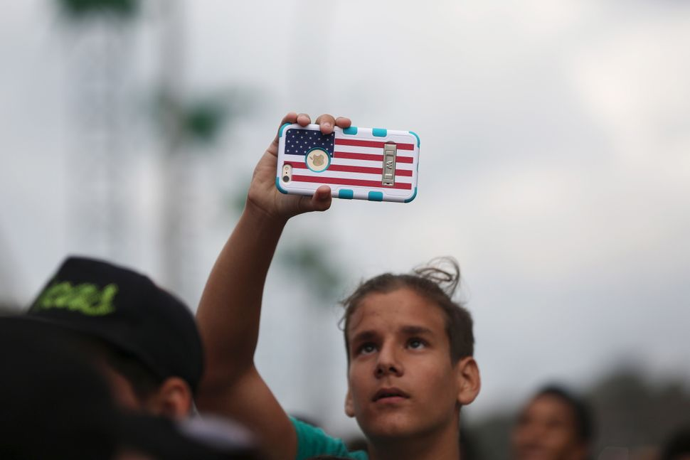 A man holds a mobile phone decorated with the U.S. flagwhile watchingMajor Lazerperform.