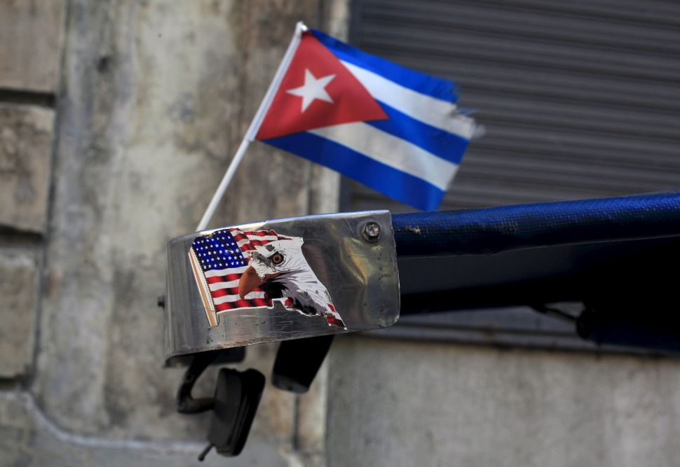 A Cuban flag and a sticker of a U.S. flag are seen on the roof of tricycle taxi in Havana.