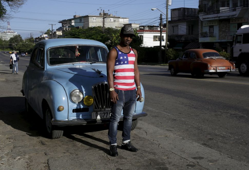 Yosuan, 26, wearing a shirt with the U.S flag, stands on a street in Havana on Feb. 22.
