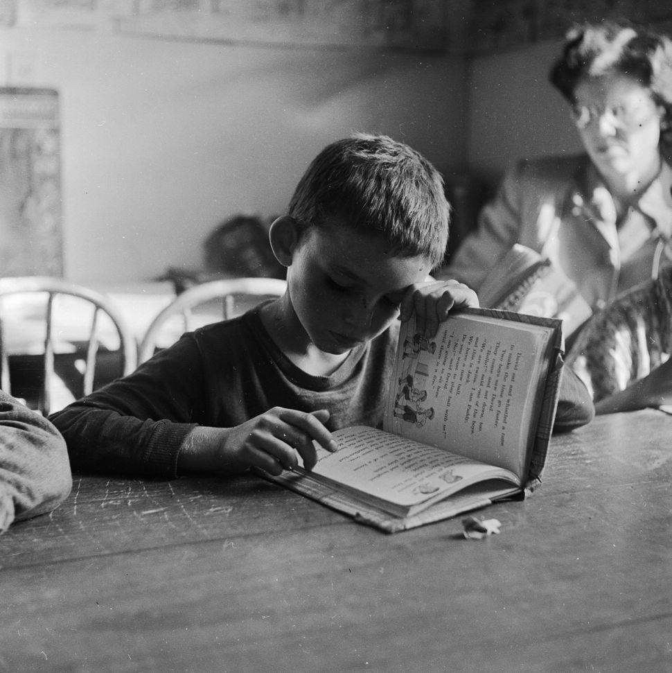A young resident at the Tascosa boys' ranch in Texas learns to read under the watchful eye of a teacher in February 1951. The