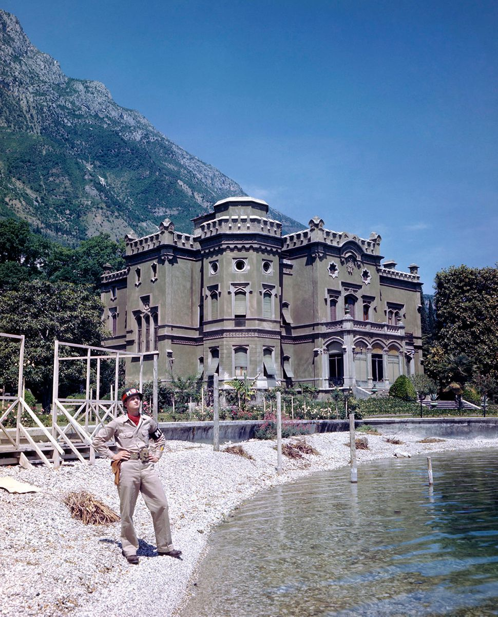 A soldier posing in front of Villa Feltrinelli, Mussolini's former residence in Gargagno. May 1945