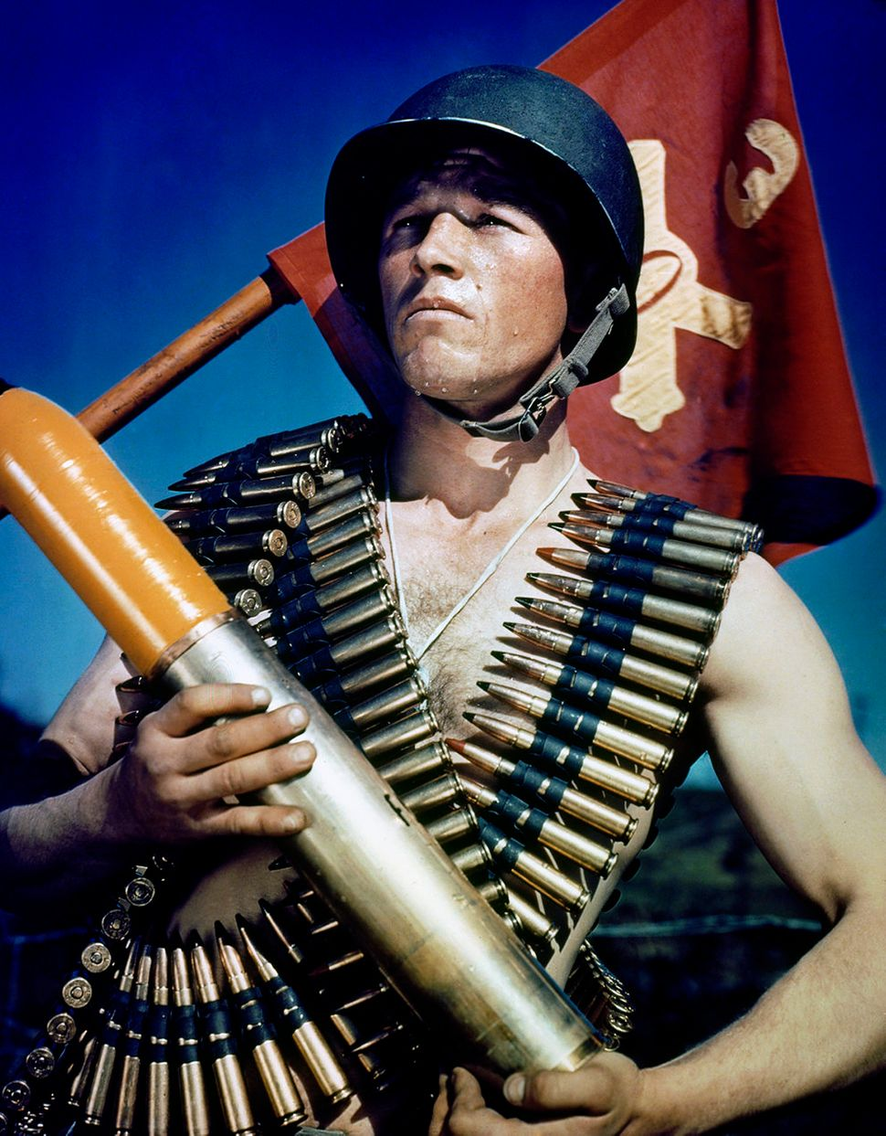 An American soldier poses, wrapped in ammunition and the artillery flag.