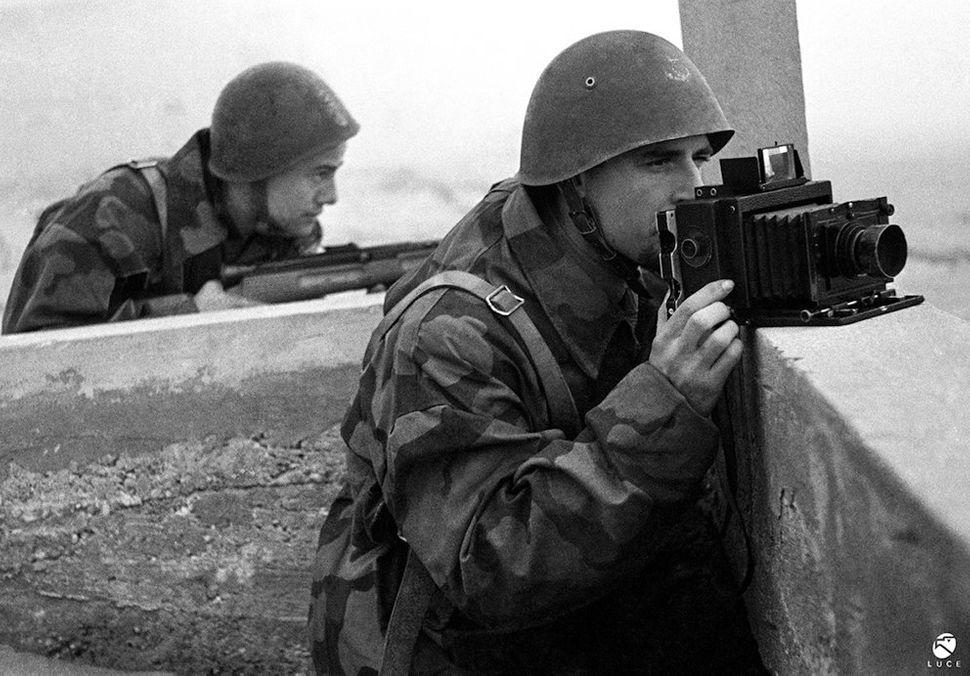 A soldier points his camera into the distance as another aims his rifle. 1944.