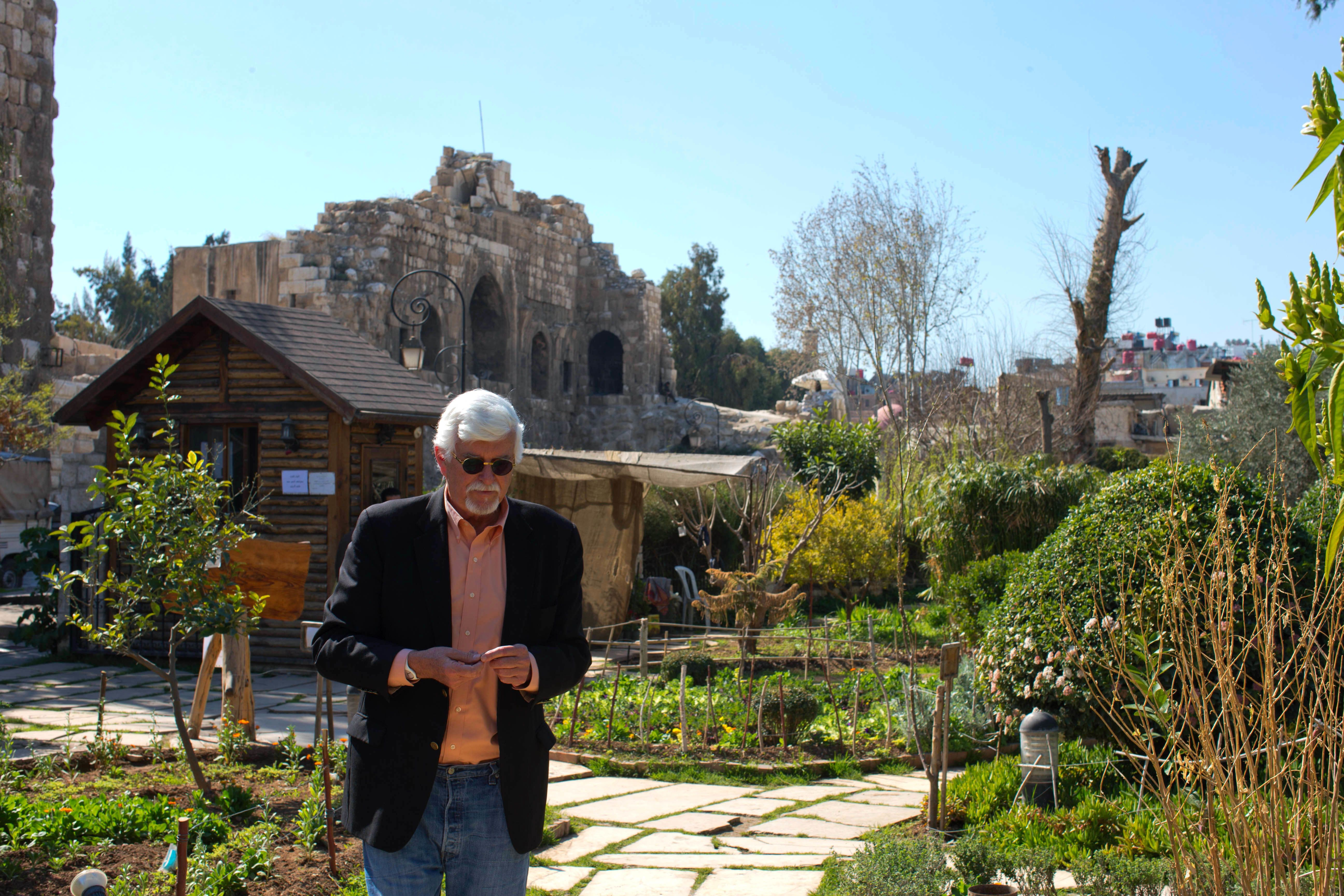 In this picture taken Monday, Feb. 29, 2016, Thomas Webber walks in a garden next to the Citadel of Damascus, Syria. Webber, an American who was born and raised in Orchard Park, New York, now has a part-time job in the English department of a local high school, where he shares his love of Charles Dickens with teenagers several times a week. The 71-year-old has no plans to leave Damascus, a city he has called home for more than four decades. (AP Photo/Hassan Ammar)