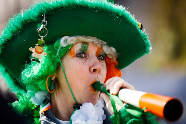 A woman dressed in colors of the Irish flag takes part in the St Patrick's Day parade through central London, England, on Mar