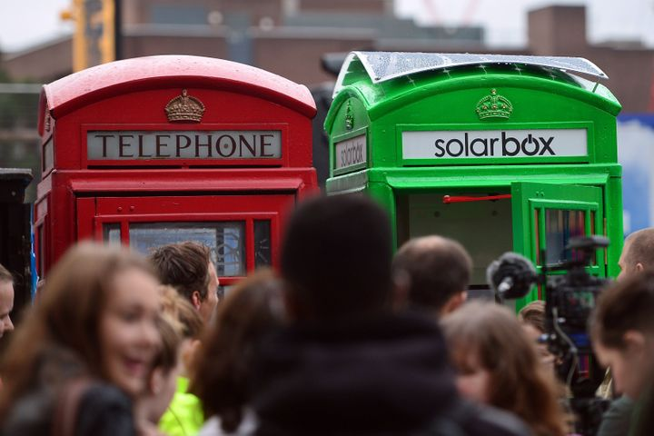 The first traditional London telephone box (R) to be transformed into a solar-powered mobile phone charger for use by the public, is pictured next to a traditional red telephone box in central London, on October 1, 2014. Use of the facility is expected to be free of charge.