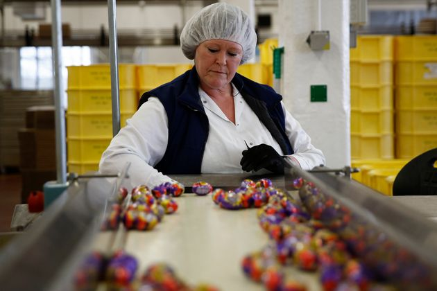 An employee monitors foil-wrapped Cadbury Creme Eggs as they move along the production line at the Bournville...