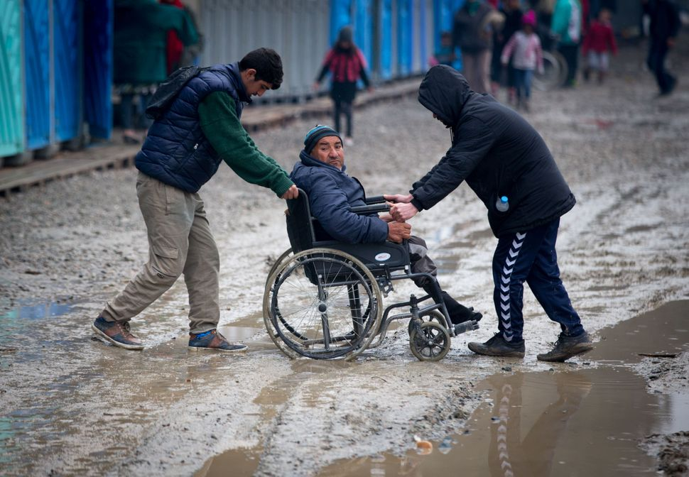 A man in a wheelchair is helped through the mud at the Idomeni transit camp.
