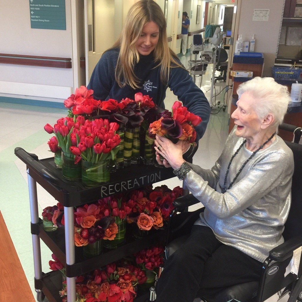 Jennifer Grove, Founder and CEO of Repeat Roses, presents flowers to Barbara, a resident of Menorah Center for Rehabilitation and Nursing Care in Brooklyn, NY.