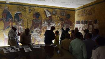 Nicholas Reeves, Antiquities Minister Mamdouh Eldamaty, and others examine the painted north wall of the burial chamber. In Reeves's theory, the right side of this wall -- the section containing the three right-most figures -- was plastered and painted atop a blocked-in passageway.