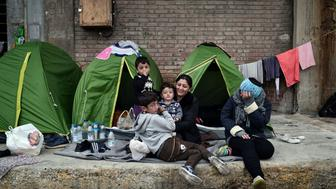 A family sit by their tents  in the port of Piraeus near Athens where thousands of refugees and migrants found a temporary shelter on March 15, 2016.  European leaders are still hopeful that a deal with Turkey can be reached, and the EU said on March 15 that it had pushed back plans to overhaul the bloc's asylum system until an accord is place.  / AFP / LOUISA GOULIAMAKI        (Photo credit should read LOUISA GOULIAMAKI/AFP/Getty Images)