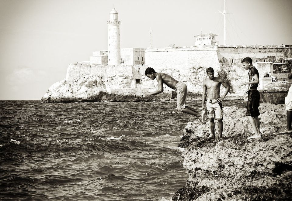 These youths are diving on the malecón (sea front drive), in front of the sixteenth century fort, El Morro, in Havana.