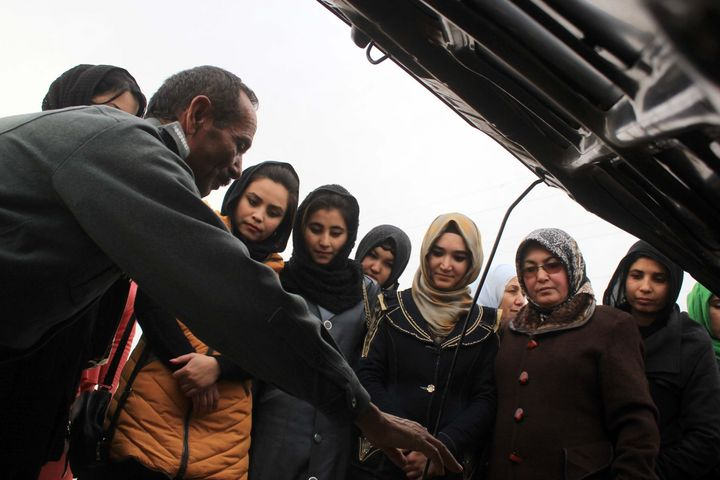 Instructors teach women taking a driving class how car engines work in Sheberghan, Afghanistan, on Jan. 20, 2016.
