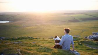 A man sits with his dog on a hillside at sunset.