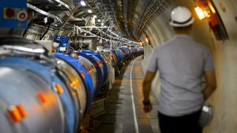 A worker walks in the CERN's Large Hadron Collider (LHC) tunnel during maintenance works on July 19, 2013 in Meyrin, near Geneva. Tests at the world's biggest collider have provided the most exhaustive confirmation to date of the Standard Model, a four-decade-old conceptual framework for fundamental particles, CERN said.   AFP PHOTO / FABRICE COFFRINI        (Photo credit should read FABRICE COFFRINI/AFP/Getty Images)