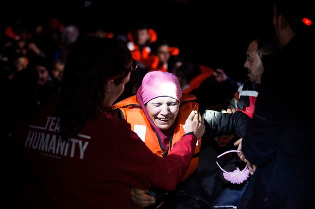 A Syrian refugee cries shortly after arriving on an inflatable boat with other refugees, crossing the...