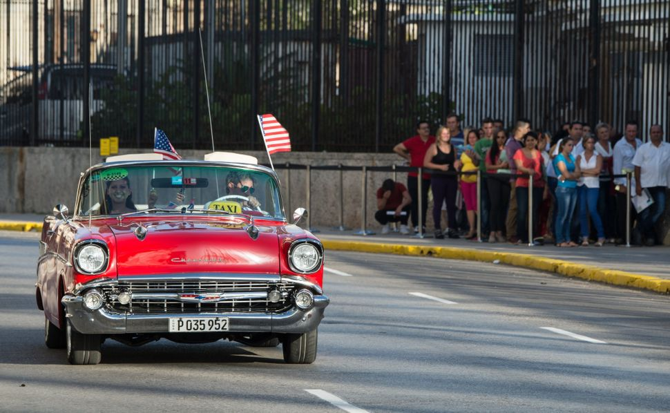 A vintage car decorated with American flags drives by the newly reopened U.S. embassy on the daythe U.S. and Cuba resto