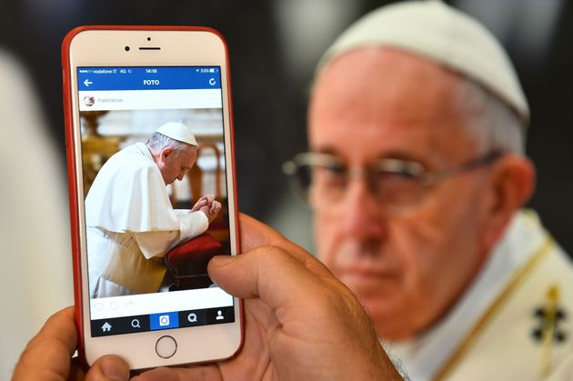 A man looks at the Instagram account of Pope Francis on March 19, 2016 in