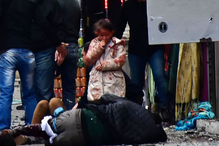 A girl cries in front of injured people in the aftermath of the blast. No group has yet claimed responsibility.