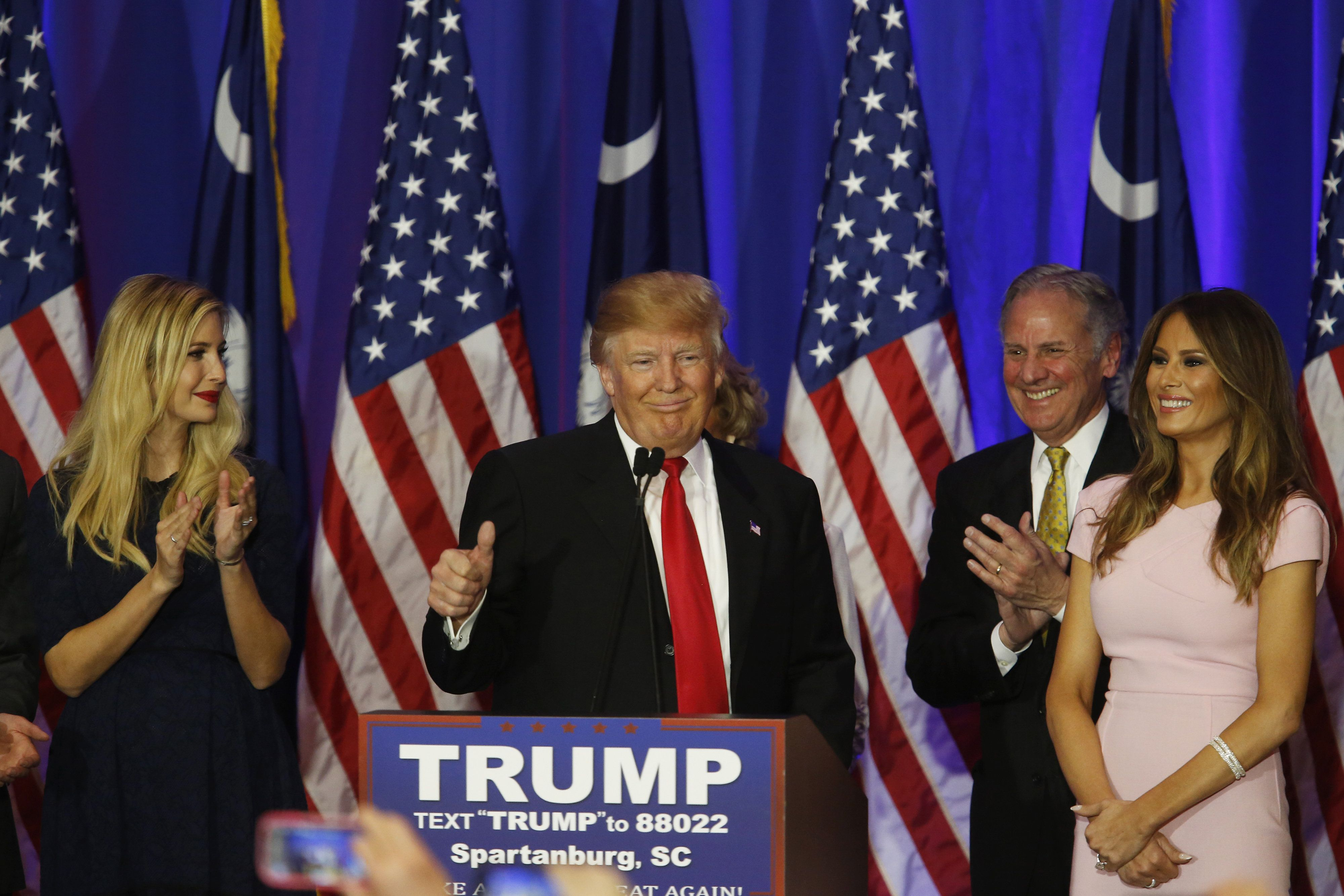 """Donald Trump, flanked by his daughter Ivanka (L) and wife Melania (R). Trump said on Saturday that they tell him to """"act pres"""