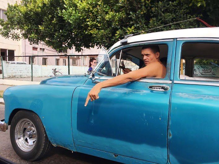 A driver in Havana gives a taxi driver directions.