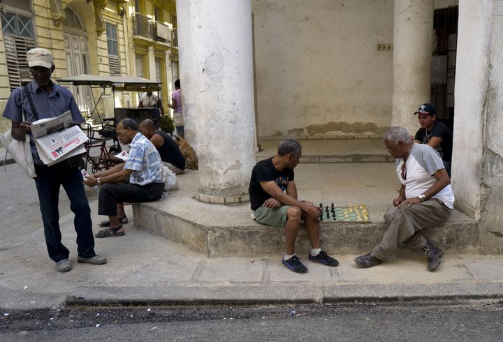 Men read the state newspaper Granma while others play chess in Old Havana on March 17, 2016. Obama arrived in Havana on Sunda