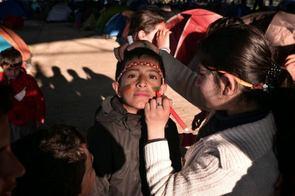 A woman paints a child's face at a makeshift camp near the village of Idomeni at the Greek-Macedonian border.
