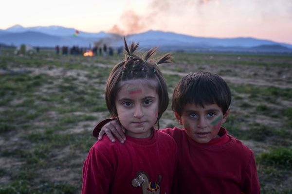 Children with face paintpose for a photo togetheras Nowruz celebrations go onin the distance in the makeshi