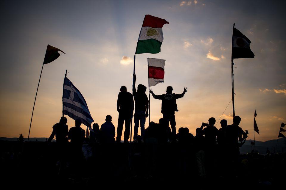 Kurdish Syrians set up Kurdish and Greek flags at the Nowruz celebrations.