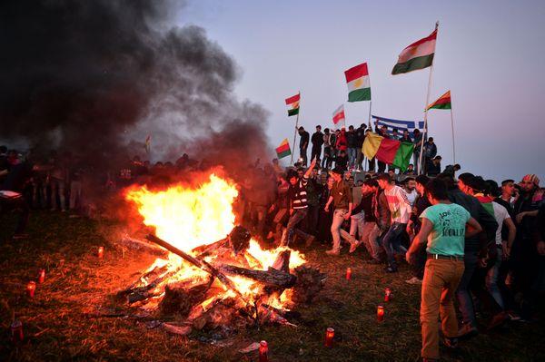 Kurds celebrate Nowruzaround a bonfire, displaying Greek and Kurdish flags.