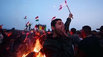 TOPSHOT - Kurds celebrate Newroz in at the makeshift camp at the Greek-Macedonian border near the village of Idomeni on March 20, 2016.  Flimsy boats packed with migrants continued to land in Greece from Turkey on March 20, 2016 despite the start of a landmark deal between the European Union and Ankara to stem the massive influx. Under the controversial deal, which came into force at midnight, all migrants landing on the Greek islands face being sent back to Turkey.  / AFP / LOUISA GOULIAMAKI        (Photo credit should read LOUISA GOULIAMAKI/AFP/Getty Images)