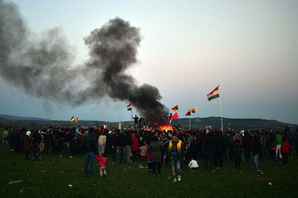 Smoke billows from a large bonfire where Kurdish refugees united in celebration.