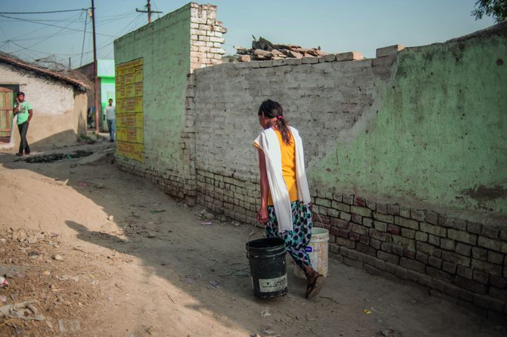 A teen on her way to collect water in Kanpur, India.