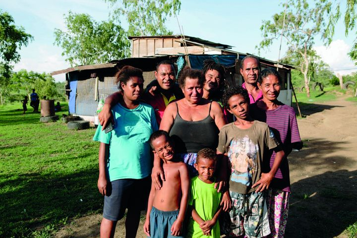 Elizabeth Ila surrounded by her family in Gereka settlement, Papua New Guinea.