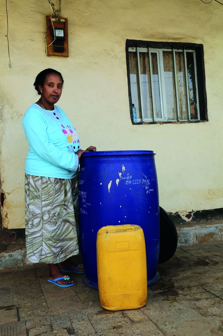 Biruktawit stands near a water container in Leku Keta, in Oromia, Ethiopia.