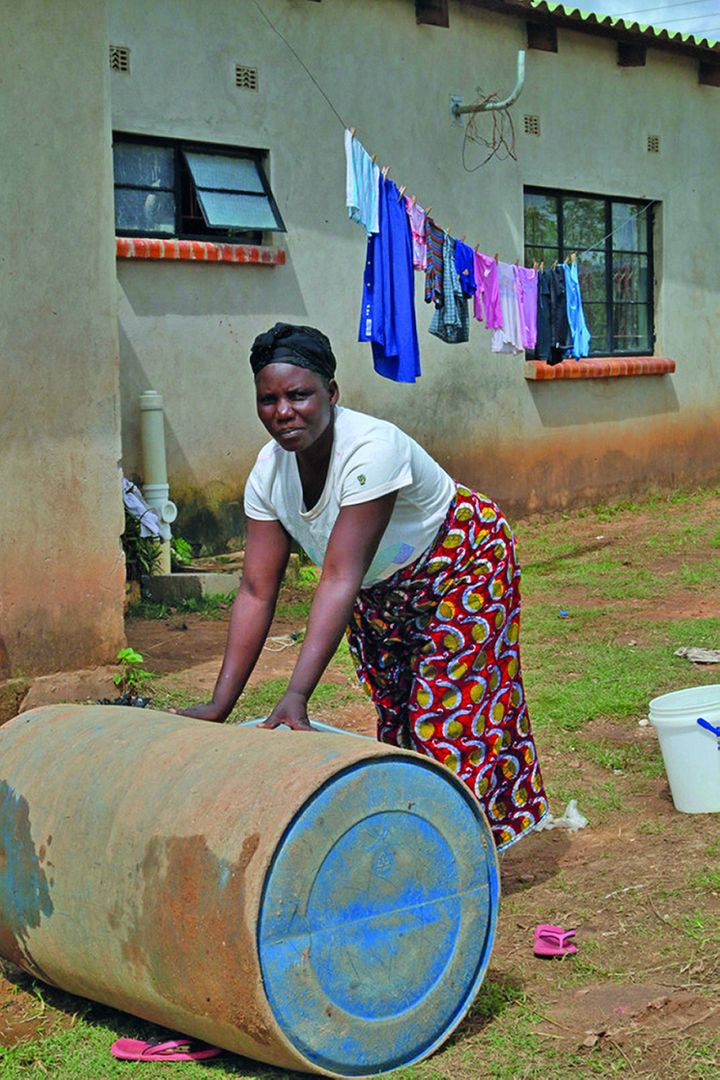 Jennifer Chikwanda rolls home a 210-liter drum of water bought from a vendor, in Lusaka, Zambia.