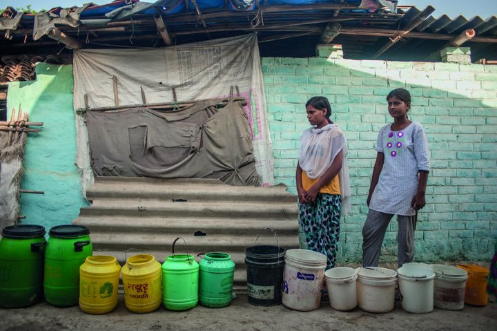 Teen girls wait at the water collection point in Nihura Basti, Kanpur, India.