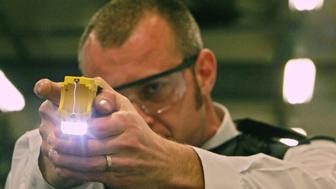 (FILES) A file picture taken on December 5, 2007 in Gravesend, Kent, shows a British police officer holding a taser gun during a training session at the Metropolitan Police Specialist Training Centre. Police forces across Britain are to be equipped with Taser stun guns after a successful pilot scheme with the controversial high-voltage weapons, officials said Monday November 24, 2008. Critics argue that the guns, which deliver a 50,000-volt charge, are 'potentially lethal,' but the government says they are crucial and is paying for 10,000 of them to be distributed around the country. AFP PHOTO/Carl de Souza/FILES (Photo credit should read CARL DE SOUZA/AFP/Getty Images)