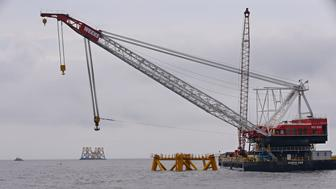ADVANCE FOR MONDAY, SEPT. 14 - FILE - In this July 27, 2015, file photo, the first foundation jacket installed by Deepwater Wind in the nation's first offshore wind farm construction project is seen next to a construction crane on the waters of the Atlantic Ocean off Block Island, R.I. With construction underway, two Louisiana firms with roots in the oil and gas industry are playing a leading part in what could be the nation's first offshore wind farm. Once it's operating next year, Deepwater Wind's Block Island project is in line to generate 30 megawatts of electricity  enough power for 17,200 homes  roughly 3 miles off Rhode Island's coast. (AP Photo/Stephan Savoia, File)