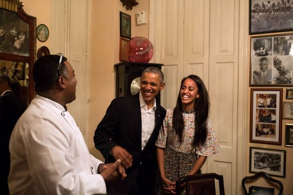 Obama shares a laugh with his daughter Malia as she interprets in Spanish for a restauranteur in Havana.