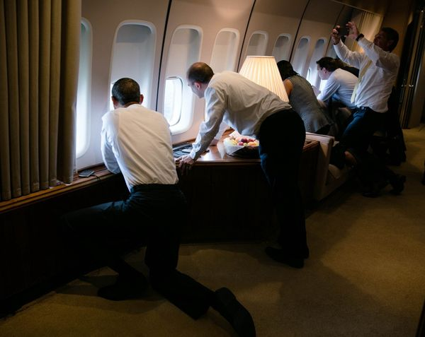 President Barack Obama joins others in looking out the window of Air Force One on the final approach into Havana.