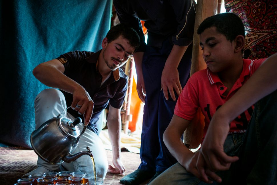Bashir, 23, pours tea for members of his family inside their tent on a farm where his family and other Syrian refugees work n